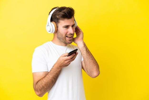Jeune bel homme caucasien isolé sur fond jaune, écouter de la musique avec un mobile et chanter