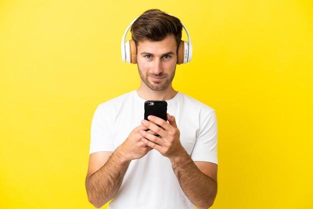 Jeune bel homme caucasien isolé sur fond jaune, écouter de la musique avec un mobile et regarder avant
