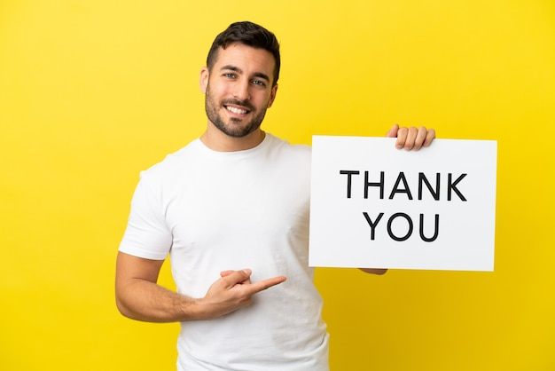 Jeune bel homme caucasien isolé sur fond jaune tenant une pancarte avec du texte merci et le pointant