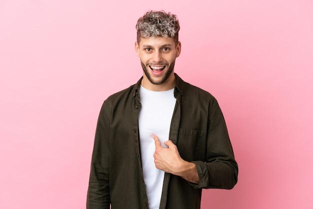 Jeune bel homme caucasien isolé sur fond rose avec une expression faciale surprise