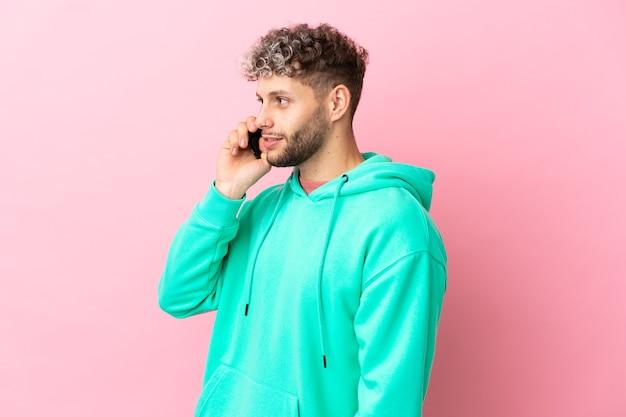 Jeune bel homme caucasien isolé sur fond rose gardant une conversation avec le téléphone portable avec quelqu'un