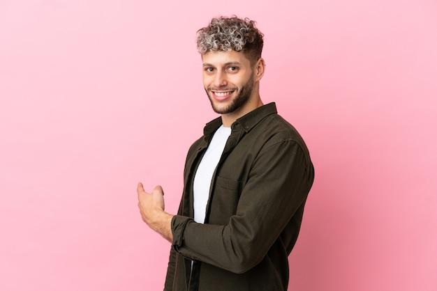 Jeune bel homme caucasien isolé sur fond rose pointant vers l'arrière