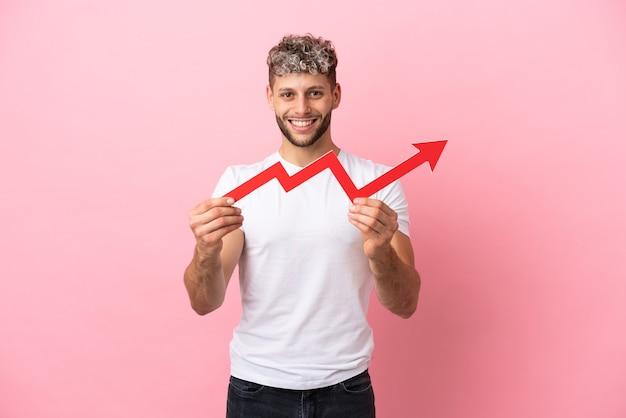 Jeune bel homme caucasien isolé sur fond rose tenant une flèche montante avec une expression heureuse