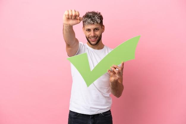 Jeune bel homme caucasien isolé sur fond rose tenant une icône de contrôle et célébrant une victoire