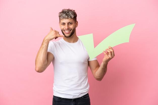 Jeune bel homme caucasien isolé sur fond rose tenant une icône de contrôle et faisant un geste de téléphone