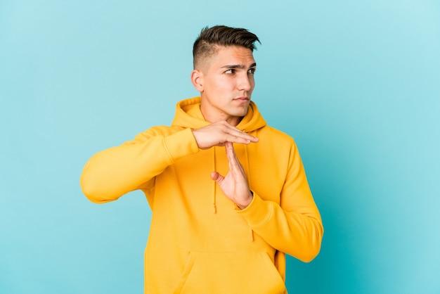 Jeune bel homme caucasien isolé montrant un geste de timeout.