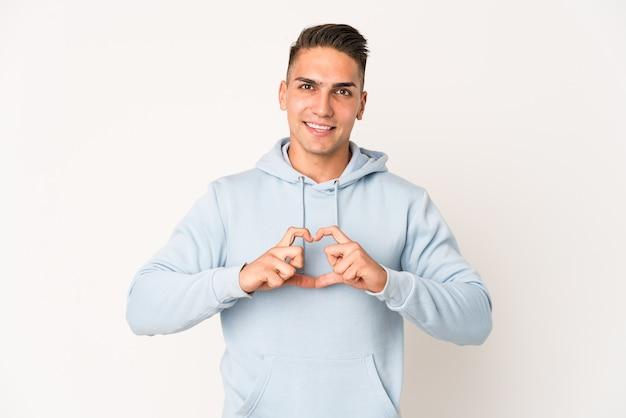 Jeune bel homme caucasien isolé souriant et montrant une forme de coeur avec les mains.