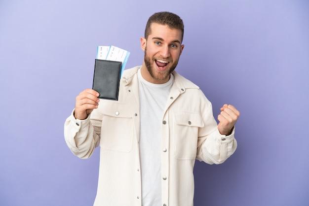 Jeune bel homme caucasien isolé sur violet heureux en vacances avec passeport et billets d'avion