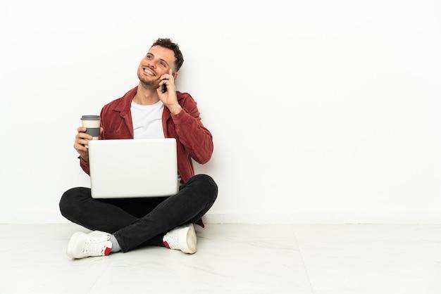 Jeune bel homme caucasien sit-in sur le sol avec ordinateur portable tenant du café à emporter et un mobile