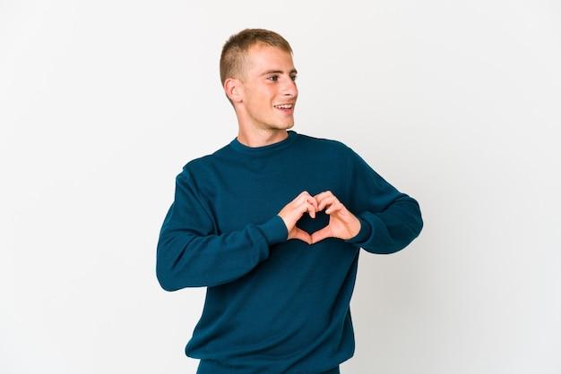 Jeune bel homme caucasien souriant et montrant une forme de coeur avec les mains.
