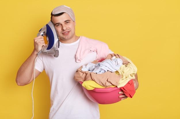 Jeune bel homme caucasien tenant le bassin avec des vêtements lavés