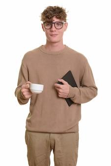 Jeune bel homme caucasien tenant un livre et une tasse de café