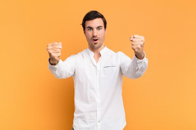 Jeune bel homme célébrant un succès incroyable comme un gagnant, l'air excité et heureux en disant: prenez ça!