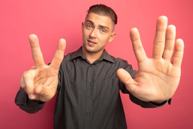 Jeune bel homme en chemise grise à l'avant souriant confiant montrant numéro sept debout sur un mur rose