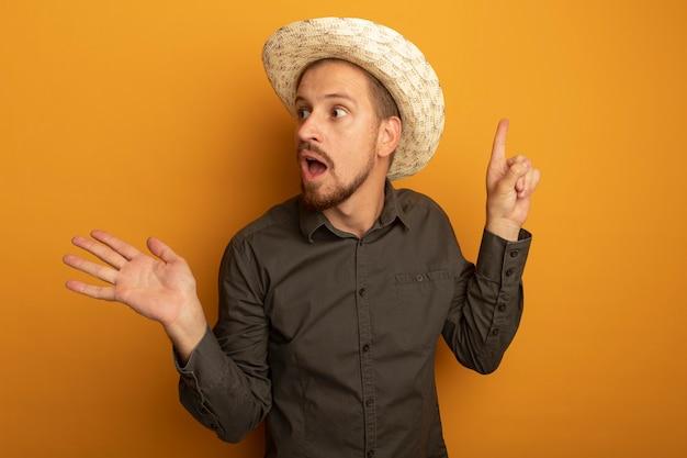 Jeune bel homme en chemise grise et chapeau d'été à côté surpris et confus présentant quelque chose avec bras et index de ferrage