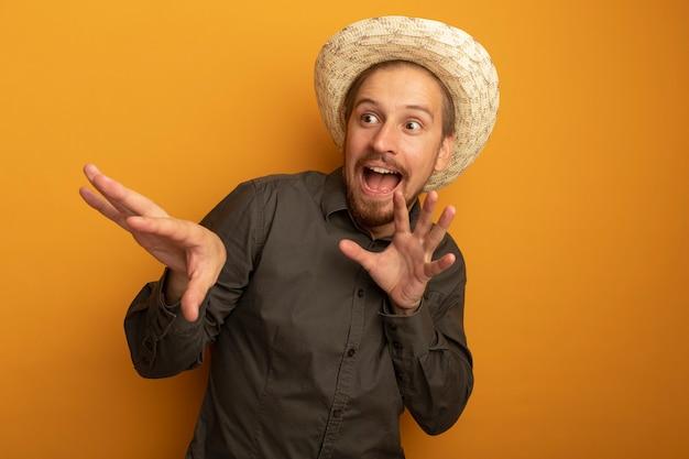 Jeune bel homme en chemise grise et chapeau d'été lookign de côté avec les bras heureux et excité