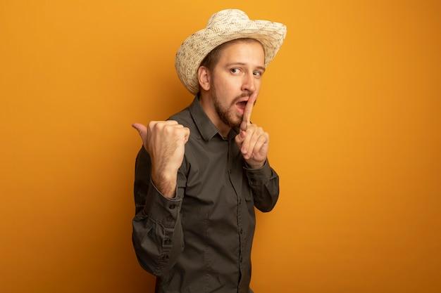 Jeune bel homme en chemise grise et chapeau d'été pointant avec le pouce en arrière faisant un geste de silence avec le doigt sur les lèvres