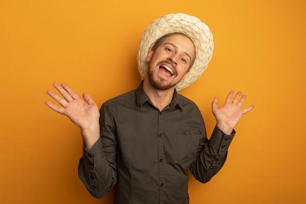 Jeune bel homme en chemise grise et chapeau d'été souriant avec un visage heureux avec les bras levés