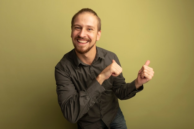 Jeune bel homme en chemise grise souriant joyeusement pointin avec les pouces en arrière