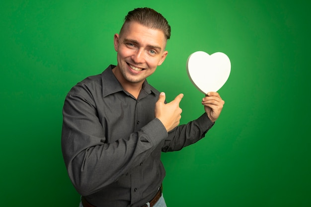 Jeune bel homme en chemise grise tenant coeur en carton pointant avec l'index sur elle souriant avec visage heureux debout sur mur vert
