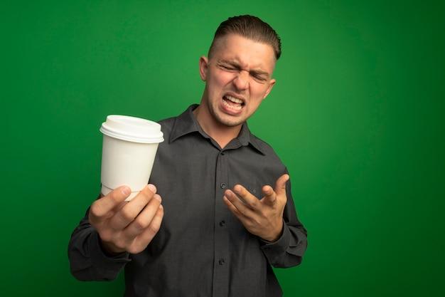 Jeune bel homme en chemise grise tenant une tasse de papier en le regardant avec le bras avec une expression dégoûtée debout sur un mur vert