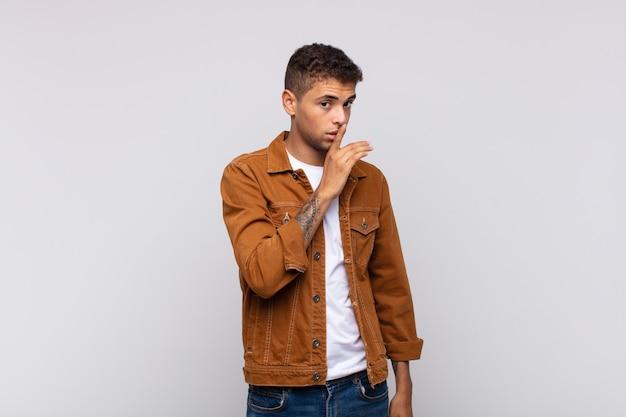 Jeune bel homme avec une chemise marron denim posant sur un mur blanc