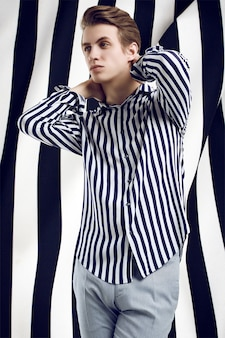 Jeune bel homme en chemise rayée pose sur noir et blanc