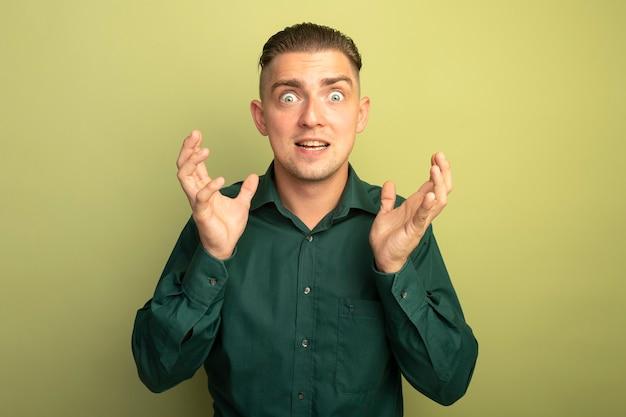 Jeune bel homme en chemise verte avec une expression agacée avec les bras levés