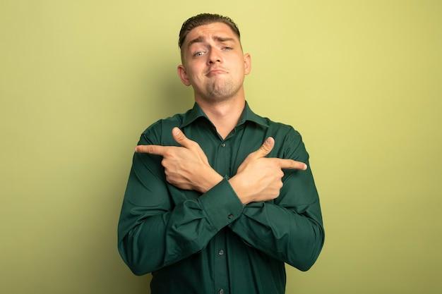 Jeune bel homme en chemise verte avec une expression confiante en traversant les mains pointant avec l'index vers les côtés opposés