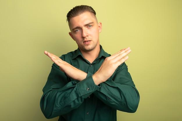Jeune bel homme en chemise verte faisant le geste d'arrêt croisant les mains avec un visage sérieux