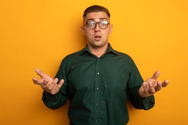 Jeune bel homme en chemise verte et lunettes confus et surpris avec les bras levés