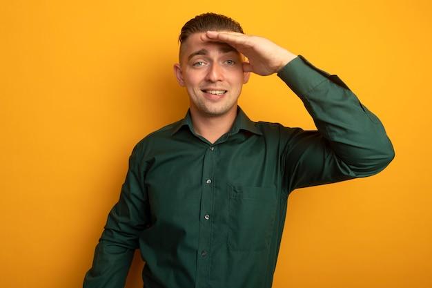 Jeune bel homme en chemise verte à la recherche de loin avec la main sur la tête pour regarder quelqu'un ou quelque chose de souriant