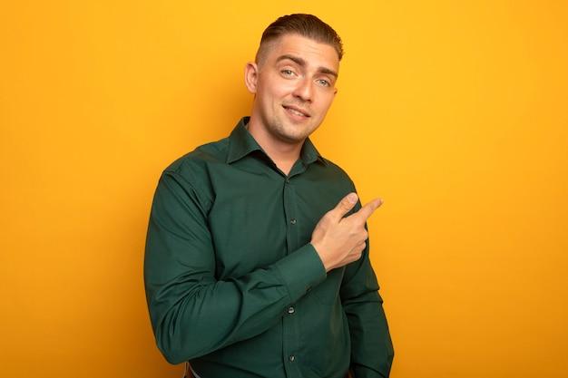 Jeune bel homme en chemise verte souriant pointant avec l'index en arrière