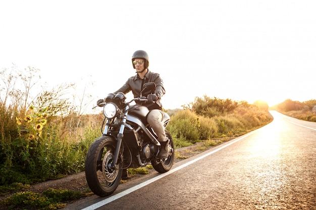 Jeune bel homme à cheval sur la moto à la route de campagne.