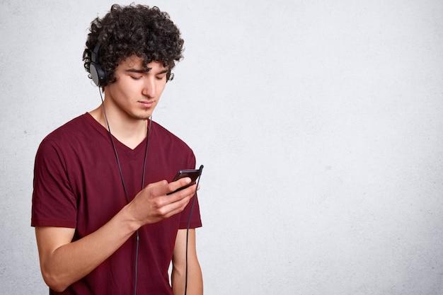 Jeune bel homme, a les cheveux bouclés noirs, gars avec téléphone portable à la main et écouteurs écoutant de la musique sur blanc avec espace de copie pour votre texte publicitaire et de promotion.