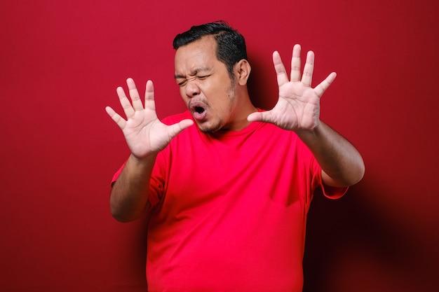 Jeune bel homme chinois portant un t-shirt rouge sur fond rouge faisant arrêter de chanter avec la paume de la main. expression d'avertissement avec un geste négatif et sérieux sur le visage.