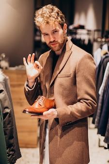 Jeune bel homme, choisir des chaussures dans un magasin