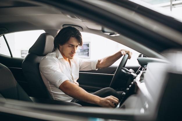 Jeune bel homme choisissant une voiture dans une salle d'exposition