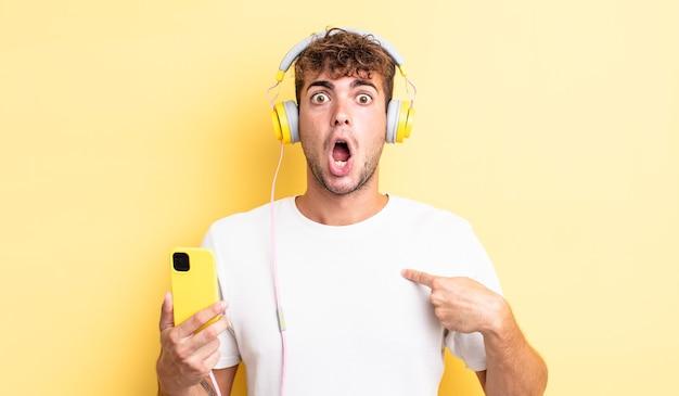 Jeune bel homme choqué et surpris avec la bouche grande ouverte, pointant vers lui-même. concept de casque et smartphone