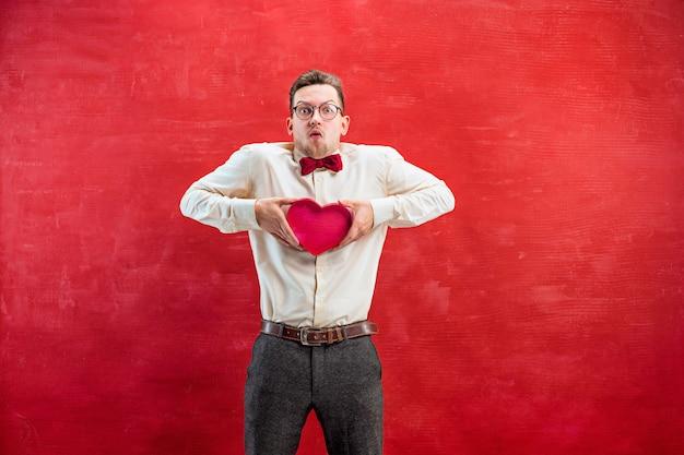 Jeune bel homme avec coeur abstrait sur fond de studio rouge