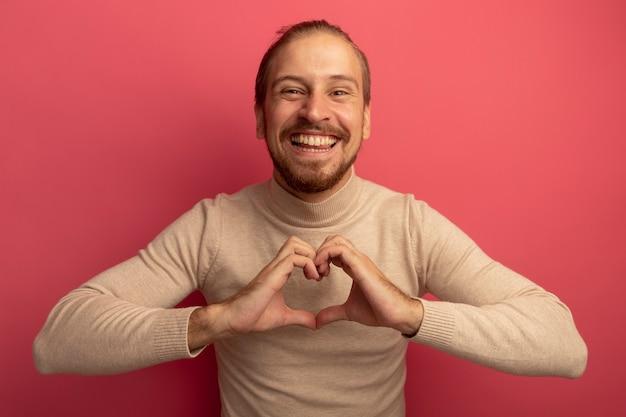 Jeune bel homme en col roulé beige faisant le geste du coeur sur la poitrine heureux et joyeux souriant debout sur le mur rose