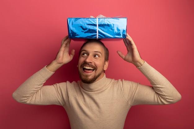 Jeune bel homme en col roulé beige tenant la boîte essentielle sur sa tête heureux et heureux en levant