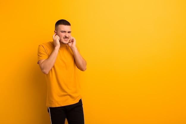 Jeune bel homme à la colère, stressé et ennuyé, couvrant les deux oreilles à un bruit assourdissant, un son ou une musique forte contre un mur plat