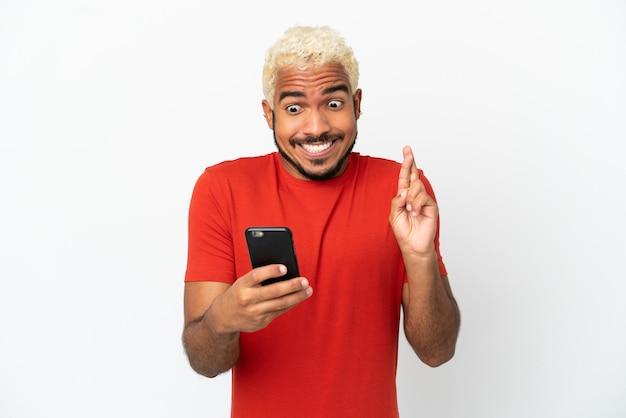 Jeune bel homme colombien isolé sur fond blanc à l'aide d'un téléphone portable avec les doigts qui se croisent