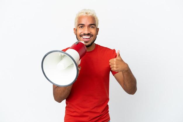 Jeune bel homme colombien isolé sur fond blanc criant à travers un mégaphone pour annoncer quelque chose et avec le pouce vers le haut