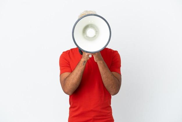 Jeune bel homme colombien isolé sur fond blanc criant à travers un mégaphone pour annoncer quelque chose
