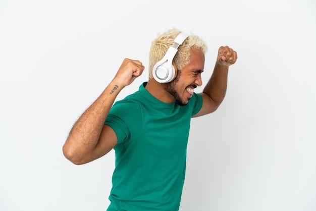 Jeune bel homme colombien isolé sur fond blanc, écouter de la musique et danser