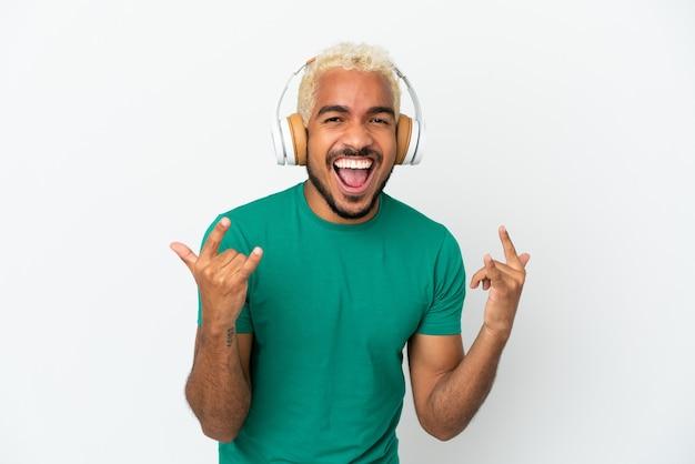 Jeune bel homme colombien isolé sur fond blanc, écouter de la musique faisant un geste rock