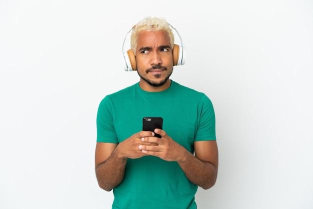 Jeune bel homme colombien isolé sur fond blanc, écouter de la musique avec un mobile et penser