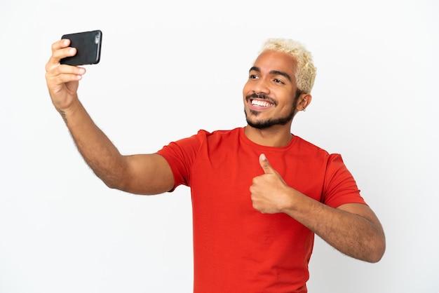 Jeune bel homme colombien isolé sur fond blanc faisant un selfie avec téléphone portable